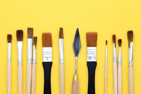 paintbrushes on yellow paper background photo