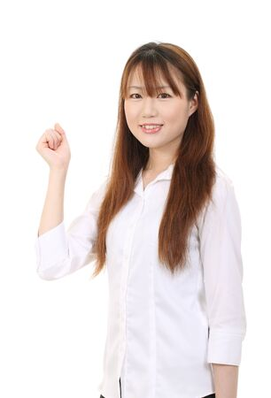 Young asian businesswoman raising her arm in sign of victory photo