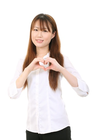 Young asian woman shows fingers heart symbol photo