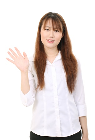 Young asian businesswoman with bye-bye gesture photo