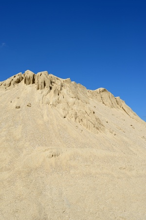 Yellow sand mound against sky photo