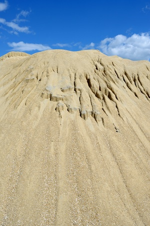 Brown sand mound against blue sky photo