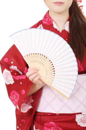 Young asian woman in clothes of kimono holding paper fan