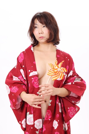 Picture of naked woman in kimono with toy pinwheel photo
