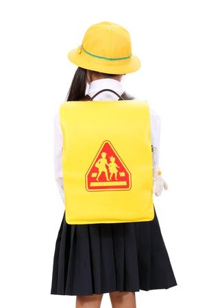 school bag: Rear view of little asian schoolgirl standing with schoolbag