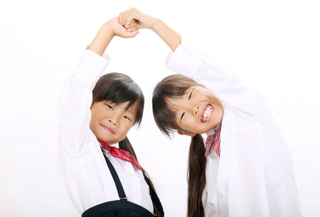 Two little asian schoolgirls holding hands  Stock Photo - 16334295