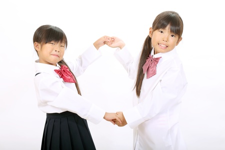 Two little asian schoolgirls holding hands Stock Photo - 16334288