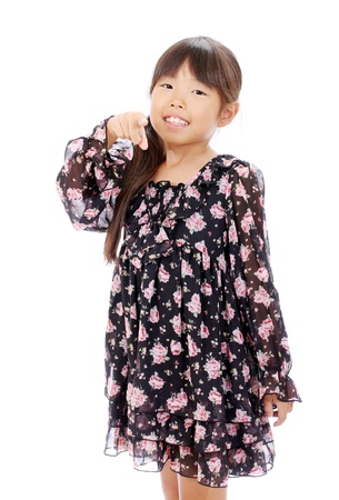 Smiling little asian girl rise hand and pointing Stock Photo - 16334301