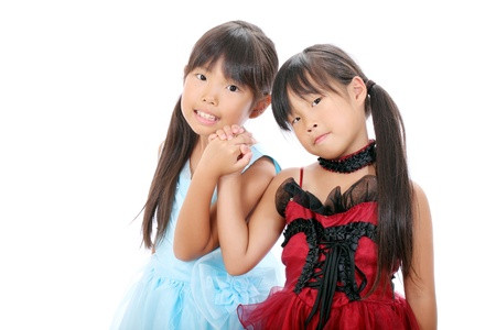 Two little asian girls holding hands and smiling  photo