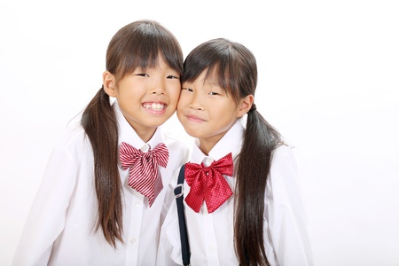 Two little Asian schoolgirls on white background photo