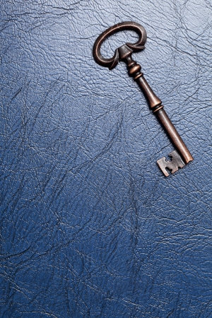 Vintage door key on a leather background photo