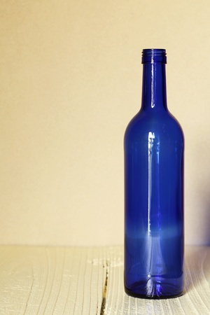 Wine bottle on wood table with wall background  photo
