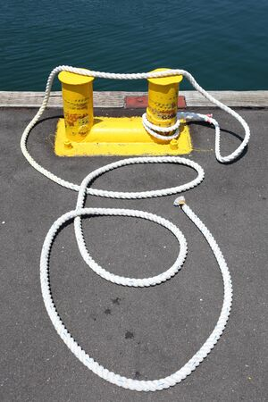 Iron bollard painted in yellow at the harbor photo