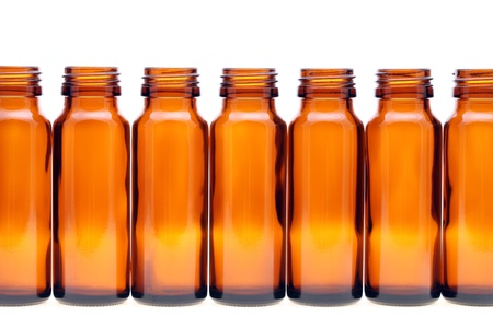 rows of brown glass bottles isolated on white background photo