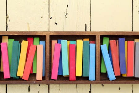 colorful crayons in a box on wooden table photo