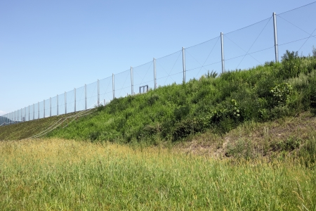 metal wire fence with blue sky in background photo
