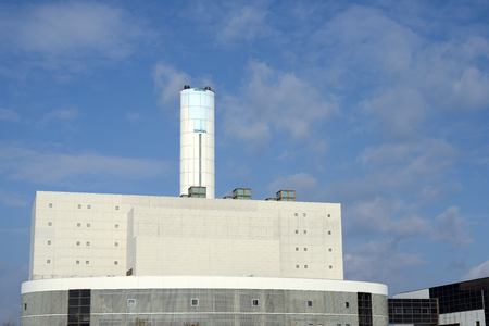 Incineration plant with chimney against blue sky photo