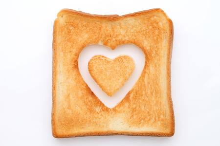toasted slice of bread with hole heart shape photo