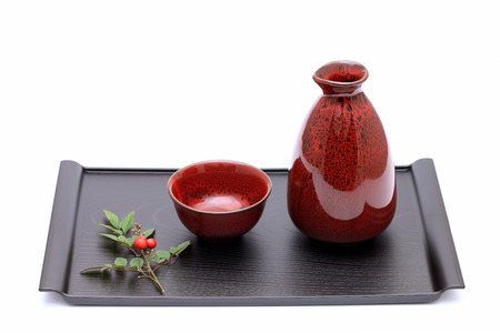 japanese sake bottle and cups on plate photo