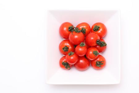 白のプレートは、白い背景の上にチェリー トマト