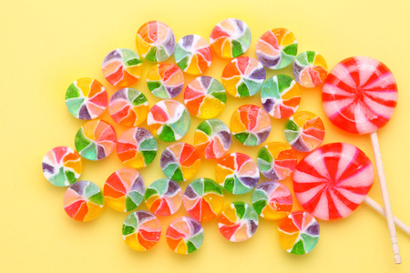 Close-up of colorful candy on yellow background photo