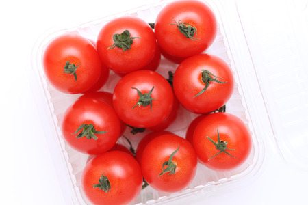 cherry tomatoes in a plastic container on white background  photo