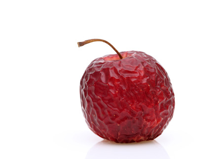 rotten fruit: Wrinkled red apple on a white background Stock Photo