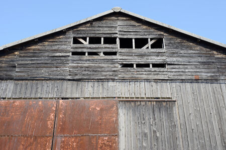 old weathered barn against a blue sky photo
