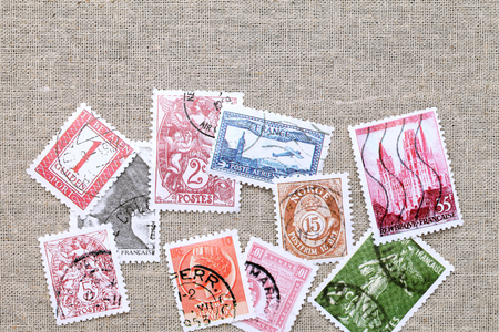 old postage stamps on burlap table
