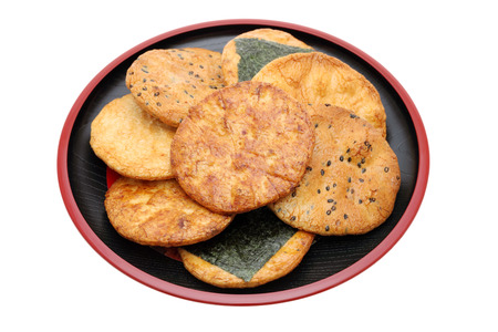 Japanese rice cracker on plate, white background