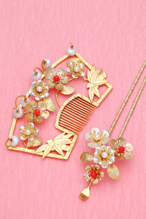 japanese flower: gold comb and hairpin on pink background Stock Photo
