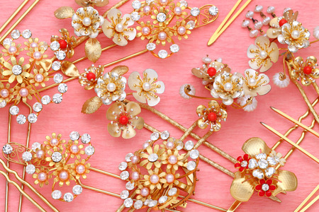 hairpin: gold hairpin with jewelry on pink background