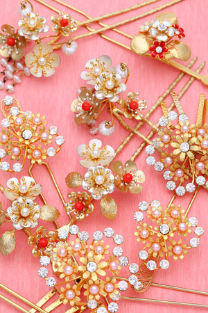 gold hairpin with jewelry on pink background photo