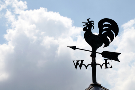 Wind cock sign silhouetted on the sky photo