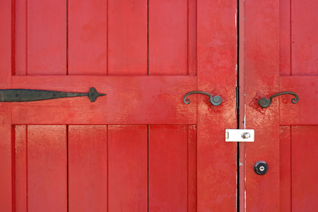 Part of old wooden red door with metal handle