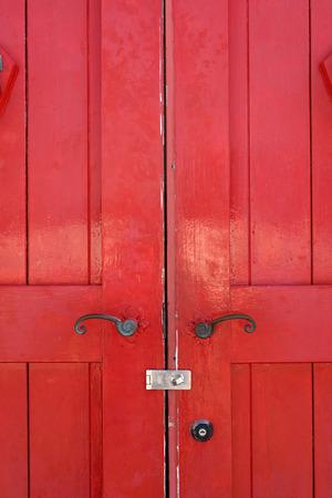 Part of old wooden red door with metal handle