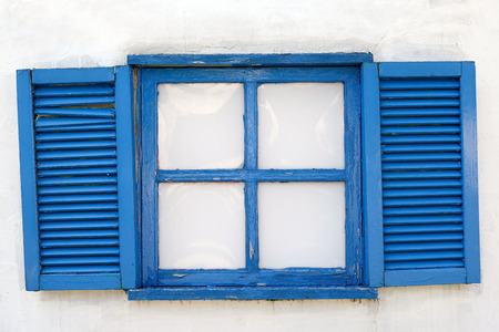 A window closed with weathered wooden shutter