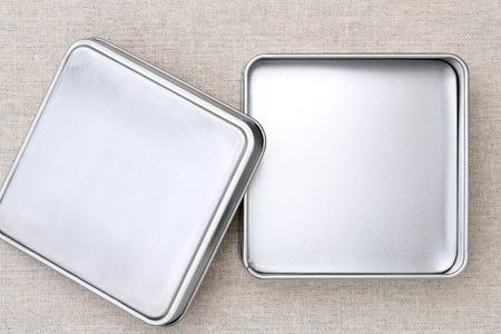 objetos cuadrados: Caja de metal sobre fondo de arpillera