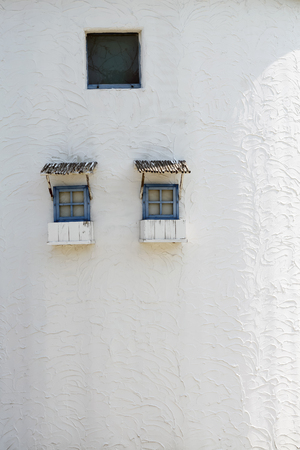 small wooden windows on the white wall with weathered photo