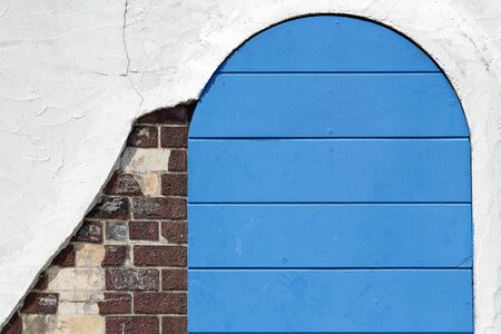 gateway: Old wooden blue gateway with white wall