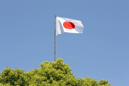 Japanese flag waving in wind against clear blue sky photo