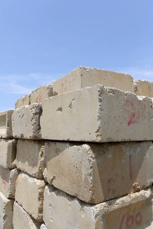cornerstone: Stack of old concrete blocks against a blue sky