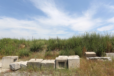 weed block: abandoned of concrete brick against a blue sky
