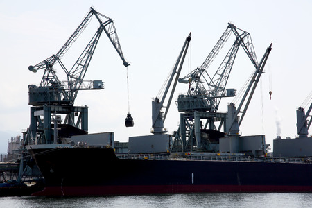 arms trade: Cargo crane freight traine and coal in port