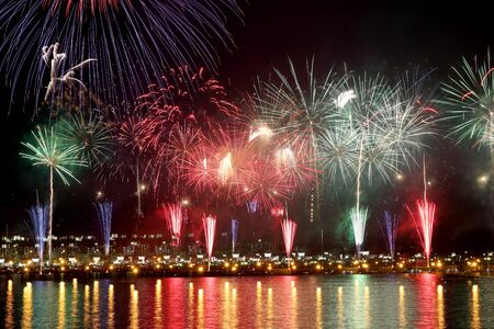 colorful fireworks reflect on sea water Stock Photo