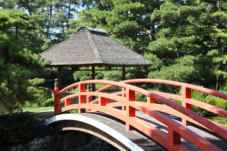 japanese tea garden: View of red wooden bridge with rest house Stock Photo
