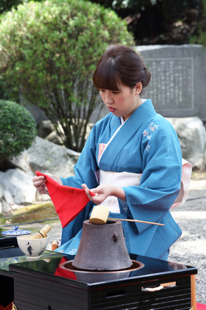 japanese tea garden: KAGAWA, JAPAN-SEPTEMBER 20, 2015: Japanese woman in traditional kimono prepares the tea ceremony at garden of the Hagiwara Temple on September 20, 2015 in Kagawa Japan. Editorial