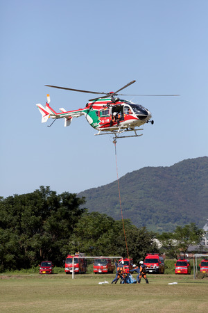 heli: KAGAWA, JAPAN-OCTOBER 8: Firemen and heli pilot works with a helicopter at the Kagawa Fire festival on October 8, 2015 in Japan.