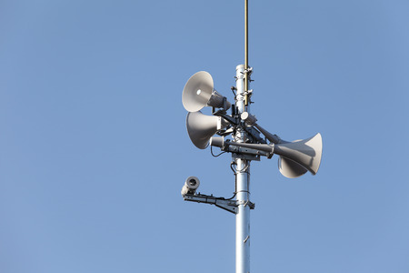 amp tower: loudspeaker of disaster-forecast against a clear blue sky