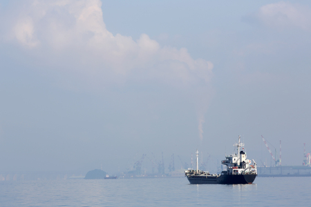 freighter: cargo freighter ship against hazy blue sky Stock Photo